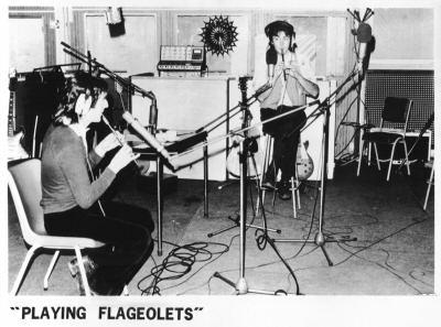 Publicity photograph for the album 'London Town', showing band members playing tin-whistles described as 'flageolets'.
