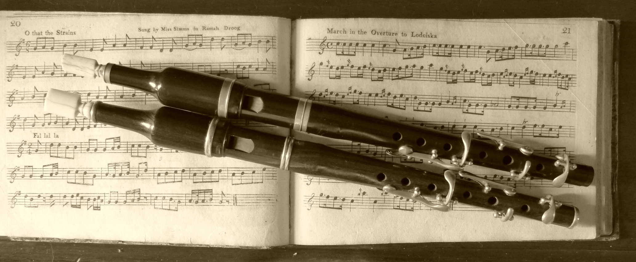 A sepia photograph of two standard English flageolets resting on some sheet music.