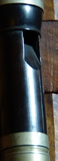 A photograph showing a closeup of a dark wood flageolet which has had a crack repaired by having the hole filled in.