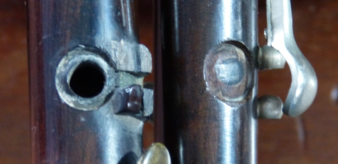 A photograph showing a closeup of a two flageolets: one has a missing key and the other has had the missing key repaired by having the hole filled in.